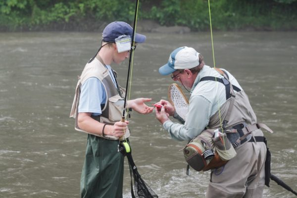 Young student angler being taught by and older fly fisherman.
