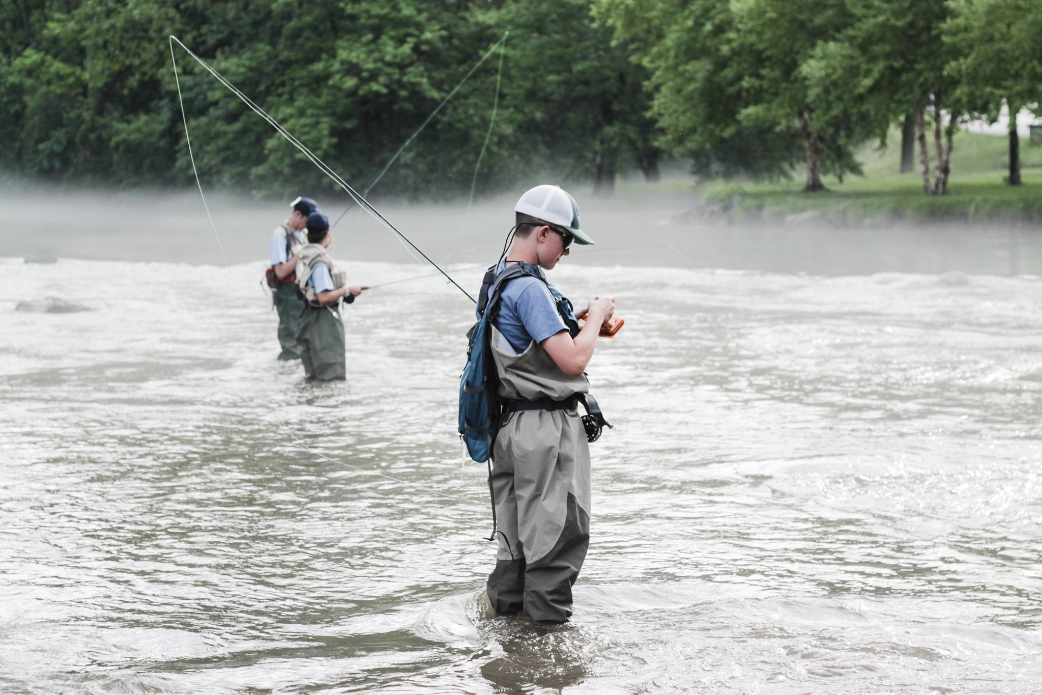 Three young anglers standing in a stream fly fishing.