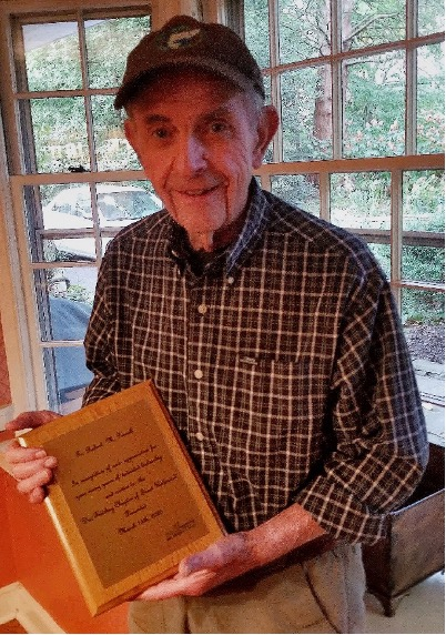 Bob Pennell holding a plaque