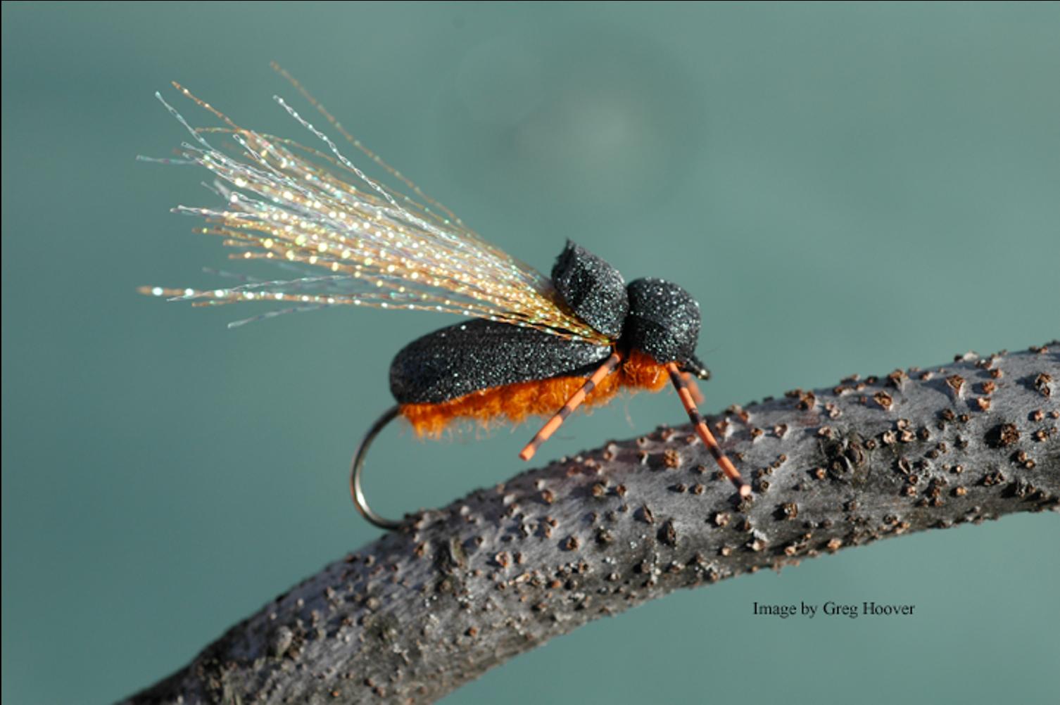 An imitation cicada fly sitting on a twig.